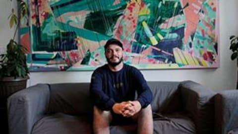 L'artiste VINO est assis sur un sofa devant l'une de ses toiles.