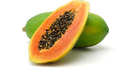 La moitié d'une papaye rouge accotée sur une papaye entière verte.