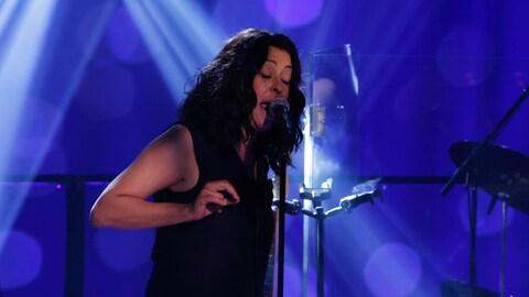 La chanteuse a les yeux fermés devant un micro.