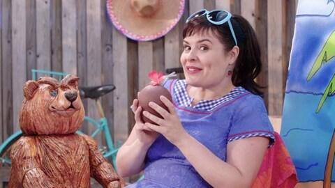 Elle tient un coco en chocolat et est assise près de l'ours