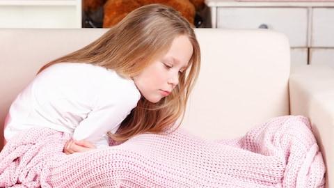 Une petite fille assise sur un fauteuil a mal au ventre.