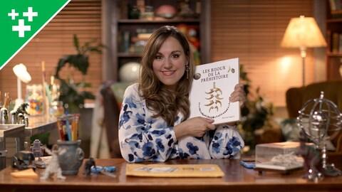 Christine montre un livre sur les bijoux de la préhistoire à la caméra.