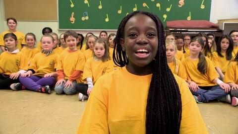 Une étudiante, vêtue d'un chandail jaune, chante devant d'autres élèves qui sont assis sur le sol.