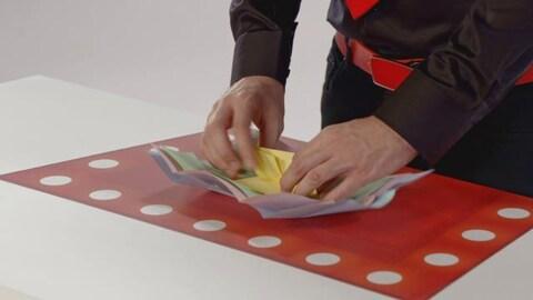 On voit les mains du magicien qui déplie une pile de feuilles de différentes grandeurs.
