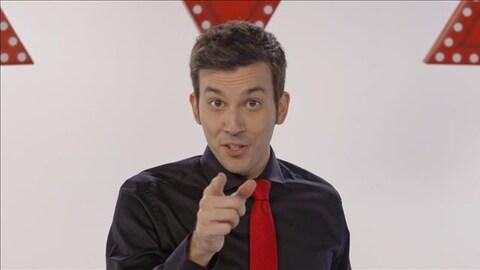 Le magicien regarde la caméra en pointant du doigt.