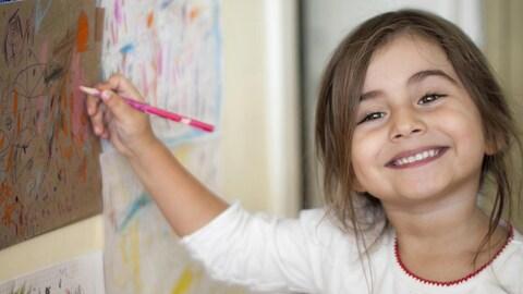 Une petite fille souriante dessine sur un mur.