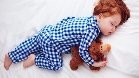 Un petit garçon est endormi en serrant un ourson dans ses bras.