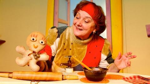 La comédienne qui interprète Claire tient la marionnette Pain d'épices sur une table avec un bol, une cuillère et un rouleau à pâte.