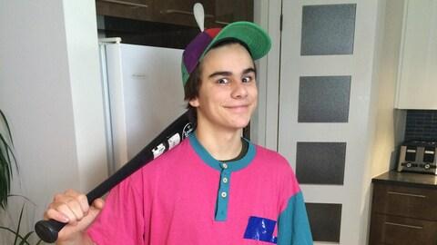 Il porte une casquette multicolore et tient une batte de baseball