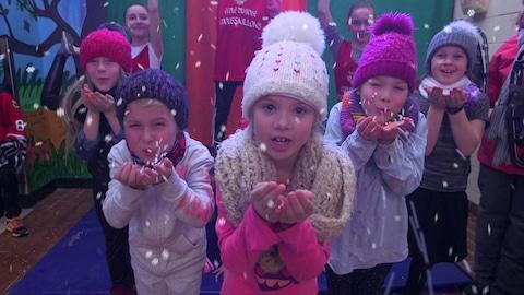 Les élèves de l'École des Moussaillons à Lévis soufflent des flocons de neige bricolés.