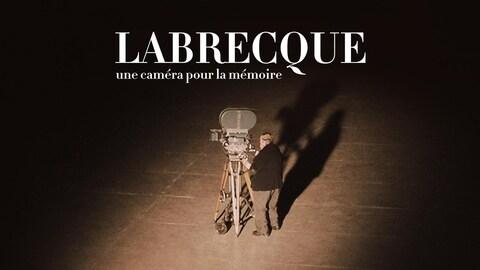 Le réalisateur est debout derrière une caméra sur un plateau de tournage.