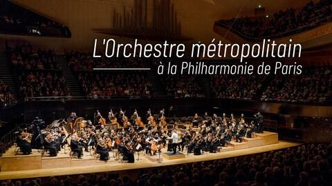 L'Orchestre métropolitain et son chez Yannick Nézet-Séguin sur la scène centrale à la Philharmonie de Paris, entouré de spectateurs.