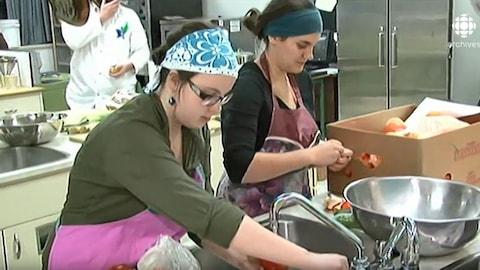Des participantes de la cuisine collective Lèche-babines à l'Université du Québec à Rimouski lavent des aliments.