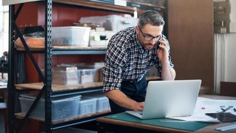 Un homme dans une petite entreprise regardent un ordinateur. Autour de lui des boites de plastique. Ceci est relié à un contenu Telus : Payez vos taxes en ligne : c'est facile et payant.