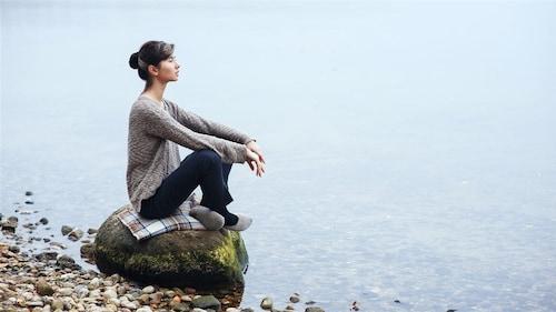 Une femme assise au bord d'un lac regarde au loin.