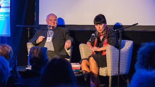 Michel Pastoureau et Nathalie Bondil assis dans deux fauteuils sur une scène et devant des micros