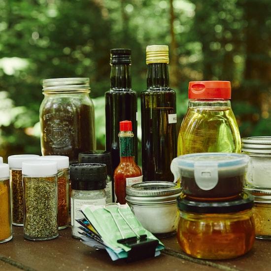 Des ingrédients non périssables dans des petits contenants sur une table à pique-nique.