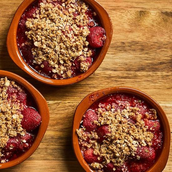 Quatre ramequins avec un crumble aux fraises.