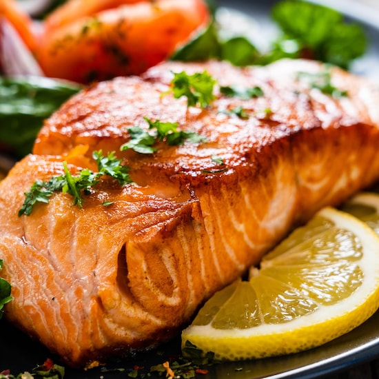 Un pavé de saumon dans une assiette avec des herbes et du citron.