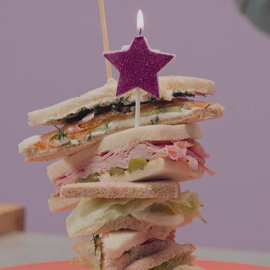 Une pile de sandwichs sans croûte: un au saumon fûmé, un au jambon et aux cornichons, ainsi qu'un aux oeufs et au wasabi.