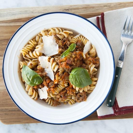 Un bol de rotinis nappés de sauce bolognaise et garnis de copeaux de parmesan et de feuilles de basilic.