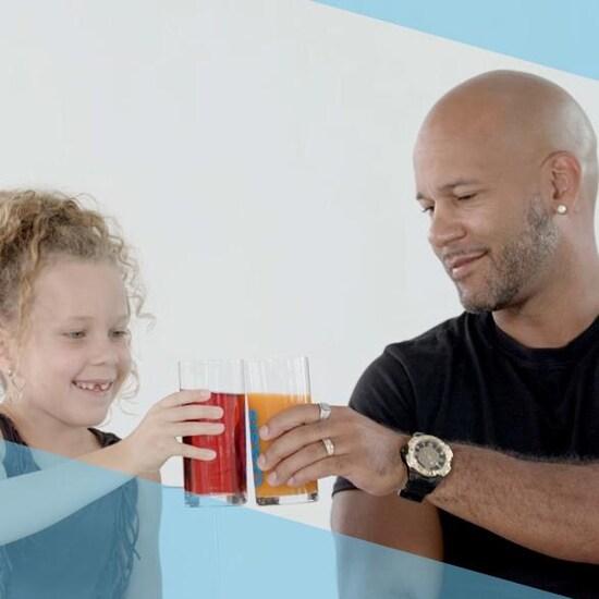 Un homme et une petite fille tapent leur verre de jus ensemble.