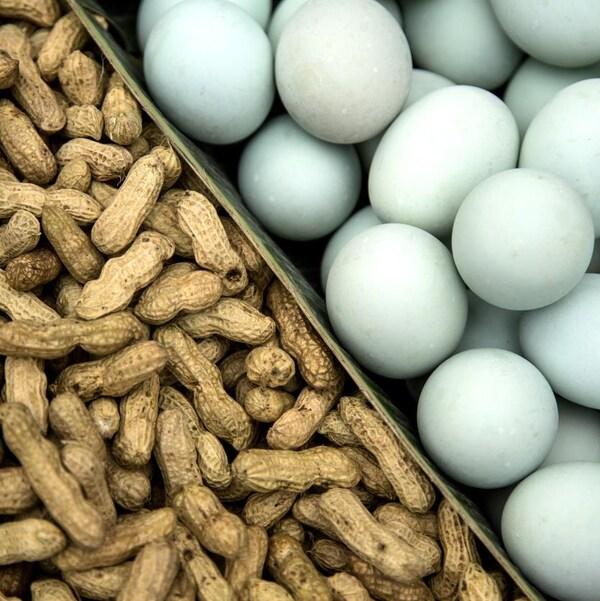 Un étal de marché avec des arachides dans leur coque et des œufs à la coquille blanche