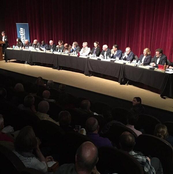 Une table avec 16 candidats et candidates sur une scène devant une foule assise dans des bancs de cinéma.