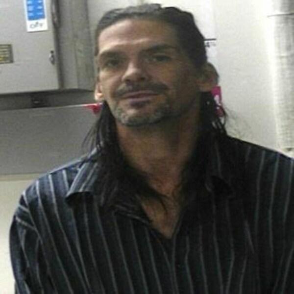 Un homme aux cheveux longs habillé d'une chemise regarde la caméra.