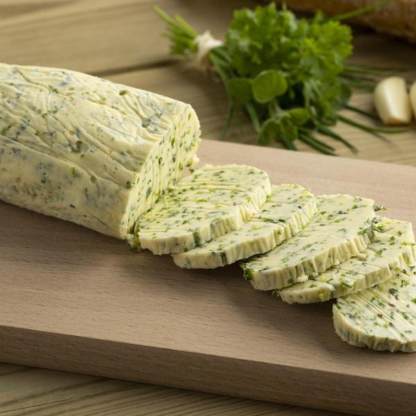Un bloc de beurre aux herbes est découpé sur une planche de bois.
