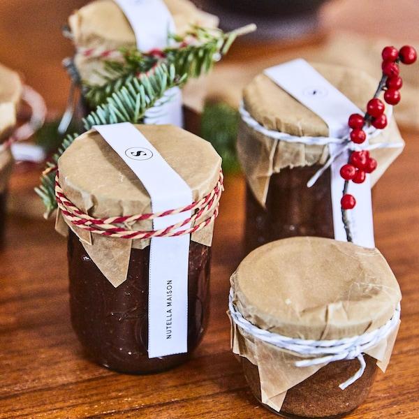 Quatre petits pots sont ornés de décorations de Noël.