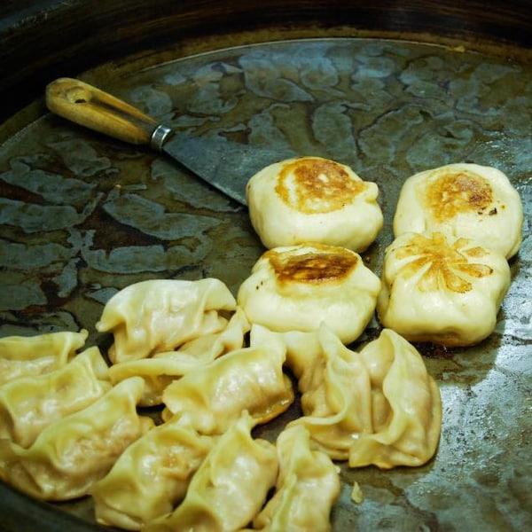 Des dumplings sont déposés sur une plaque chauffante.