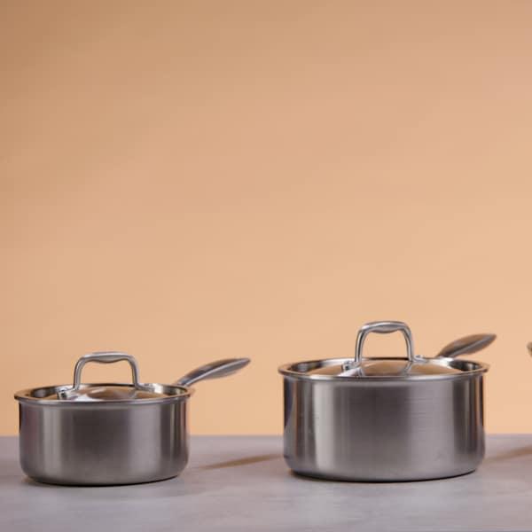 Une petite casserole, une grande casserole et un faitout sont posés sur une table de travail.