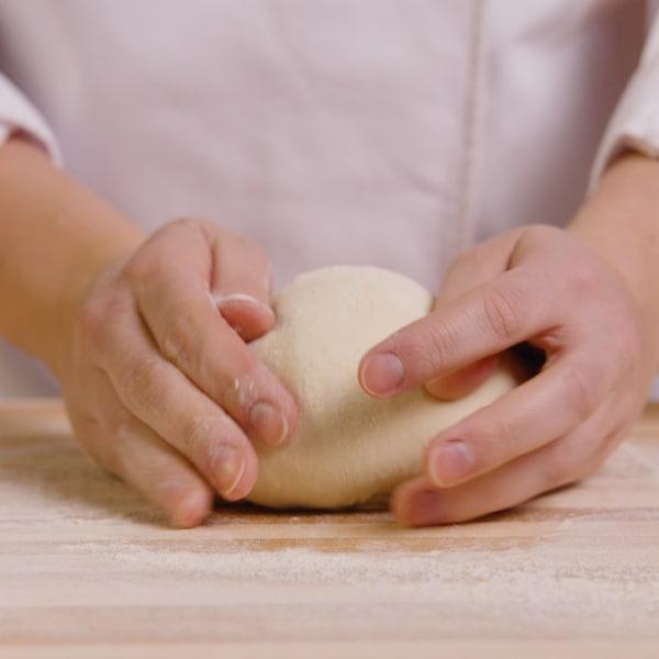 Une personne pétrit une boule de pâte à pain sur un ilot bien enfariné.