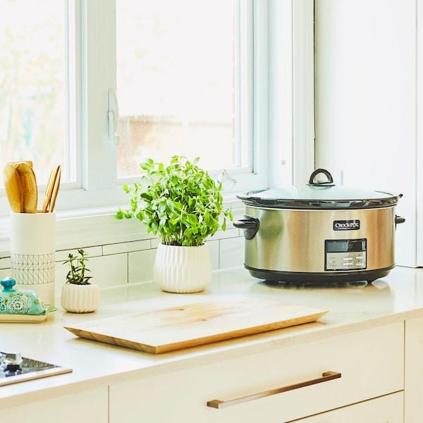 Dans une cuisine ensoleillée, une mijoteuse fonctionne.