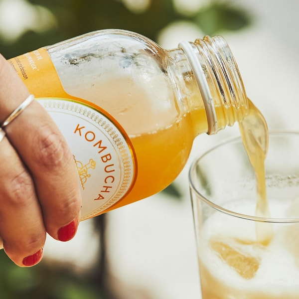 Une main féminine verse un verre de kombucha.