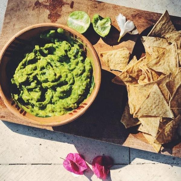 Un bol de guacamole et des croustilles de maïs sont déposés su rune planche de bois.