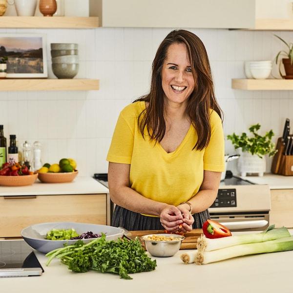La nutritionniste Geneviève O'Gleman porte un chandail jaune et tient des légumes dans ses mains en souriant à la caméra. Plusieurs aliments sont déposés sur le comptoir de cuisine.