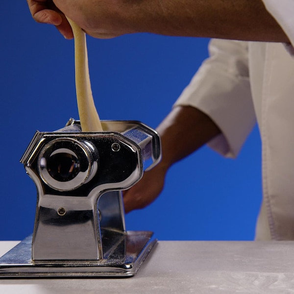 Une personne utilise un laminoir pour les pâtes.