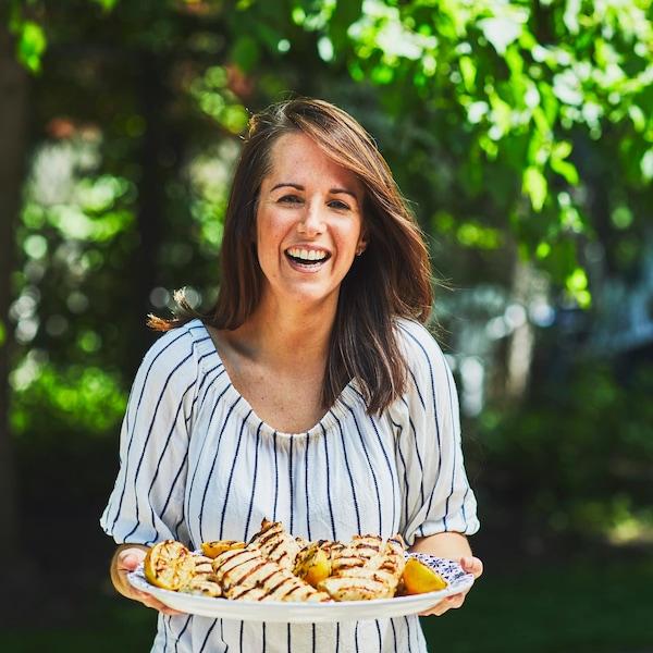 Geneviève O'Glement tient dans ses mains un plat de service. Dans celui-ci  il y a des poitrines de poulet grillées et des citrons grillés coupés en deux.