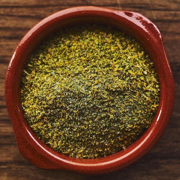Le sel aromatisé dans un petit plat de terre cuite sur un comptoir de bois.