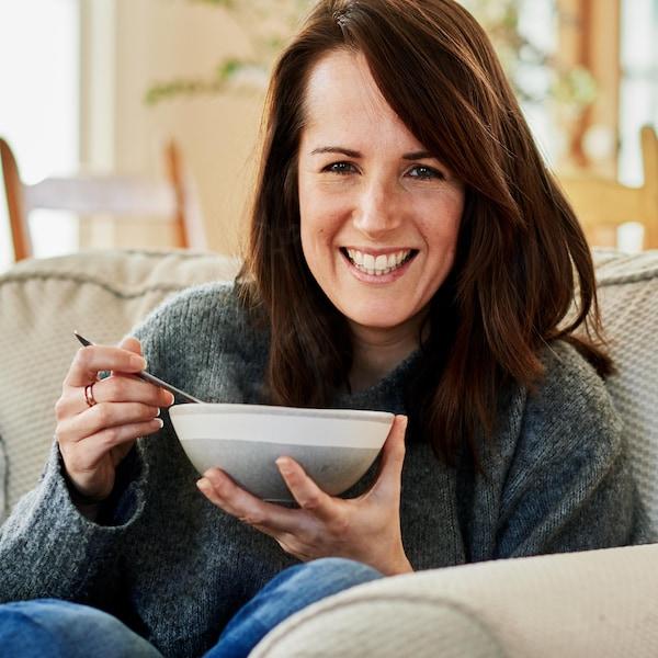 Geneviève O'Gleman tient un bol de soupe dans ses mains. Elle assise dans un fauteuil en tissu moelleux.