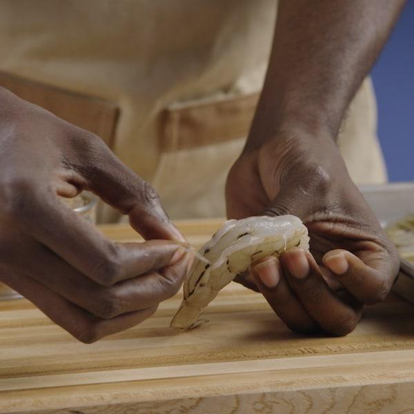 Une personne retire l'intestin d'une crevette.