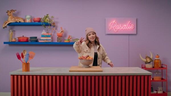 Rosalie est debout derrière un ilot de cuisine et montre avec ses doigts le chiffre 3.