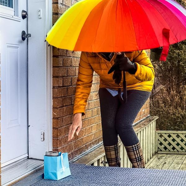 Devant le perron d'une maison,  à l'abri sous un parapluie, une personne est penchée pour prendre  un sac cadeau contenant de la nourriture.