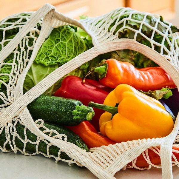 Des courgettes, des poivrons et un chou sont dans un sac tressé posé sur le dessus d'un îlot de cuisine.