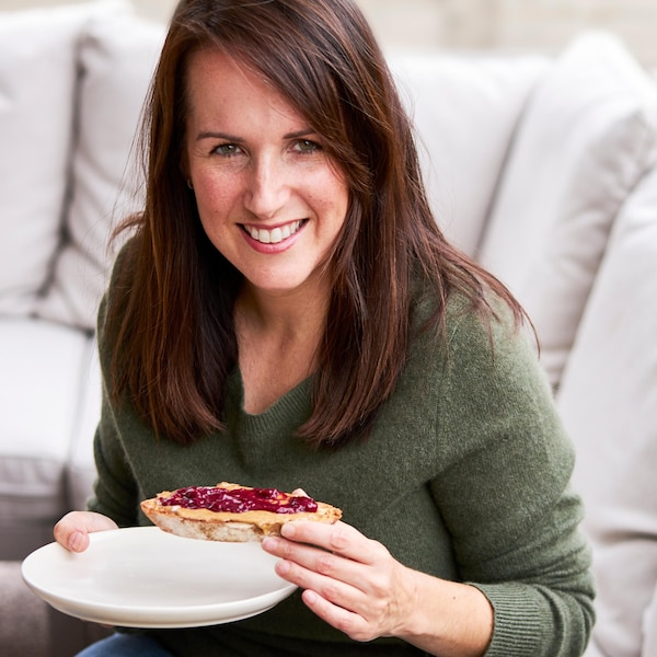 Geneviève O'gleman déguste une rôtie de blé entier tartinée de beurre d'arachides et une couche de confiture.