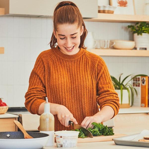 Adolescente qui cuisine une recette au plan de travail et qui coupe du kale.