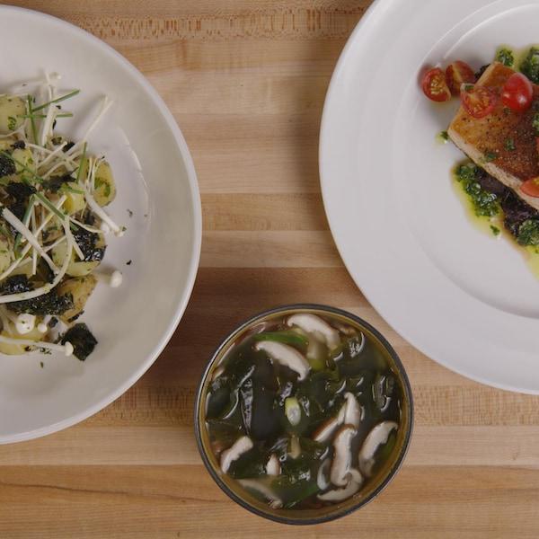 Trois plats reposent sur un ilôt de cuisine.