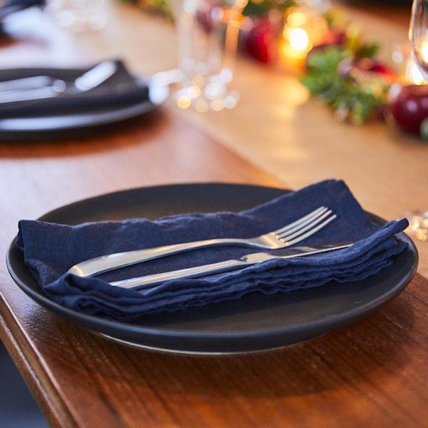 Assiette foncée avec serviette en tissu bleu et couvert sur le dessus.